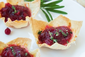 Cranberry brie mini tarts with a sprig of rosemary on a wooden table